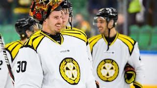 Brynäs målvakt Joacim Eriksson ler mot sina lagkamrater, med hjälmen uppdragen på huvudet.