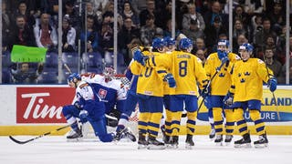Svenska spelare samlas i en gruppkram framför Slovakiens målvakt