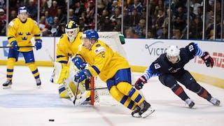 Erik Brännström i gul svensk tröja driver pucken och jagas av en amerikansk spelare. i bakgrunden syns den svenska målvakten och en annan svensk back.