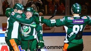 Tre glada spelare i Färjestads gröna matchdräkter jublar och kramar om varandra vid sargen