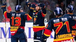 Dick Axelsson har just gjort mål och jublar med armarna uppåt och med ett leende på läpparna. Flera medspelare är på väg fram för att gratulera.