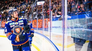 Glad Växjöspelare i blå tröja åker i ena sarghörnet, tittar upp mot sin hemmapublik som syns i bakgrunden, och lyfter klubborna som tack för stödet.