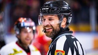 SHL-domaren Emil Yletyinen i svartvitt ställ ler brett och tittar i riktning mot kameran, i bakgrunden skymtas en spelare.