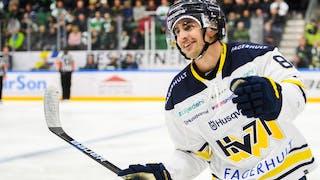 Nils Andersson i vit HV-tröja ler, och höjer armen i skyn i glädje.