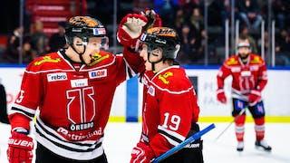 Två Örebro-spelare i röda tröjor gör high five i förgrunden. I bakgrunden ansluter en tredje Örebro-spelare.