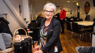 Harriet Widmark står uppställd intill sitt fikabord med pressrummets bord och stolar i bakgrunden.