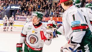 Frölundaspelare i vit tröja gör high five med målvakt på avbytarbänken. I bakgrunden ses ytterligare Frölunda-spelare och Växjöpublik