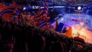 Översiktsbild av Vida Arena med isen till höger i bild och i förgrunden syns den fyllda läktaren med flaggor.