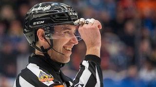 Närbild i profil på Linus Öhlund, som ler brett och lyfter sin högra hand i höjd med ansiktet.