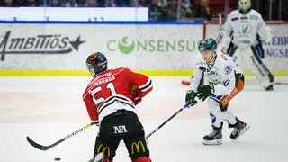 Örebros nummer 51 Kristian Näkyvä, med ryggen vänd mot kameran, i duell med en vitklädd Färjestadsspelare.