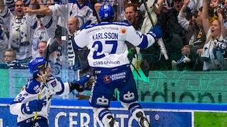 Leksands Anton Karlsson i vit tröja och blåa byxor hoppar i glädje upp mot plexiglaset framför extatiska hemmafans
