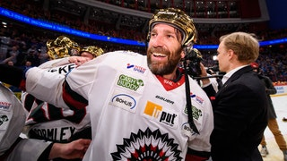 Joel Lundqvist i guldhjälm ler med medspelare och en fotograf i bakgrunden